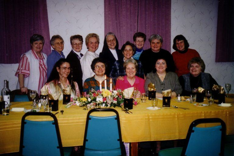Photograph of Maureen Gallagher seated at a table surrounded by other women.