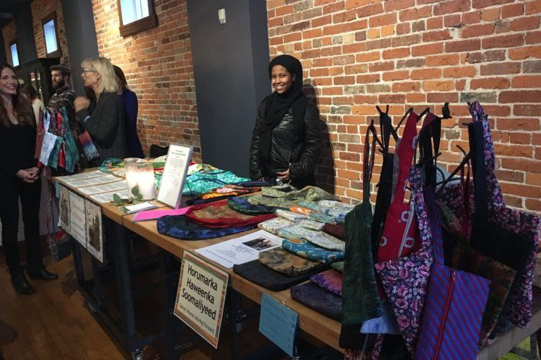 Photograph of a woman standing behind a table selling bags that she has hand-sewn herself.