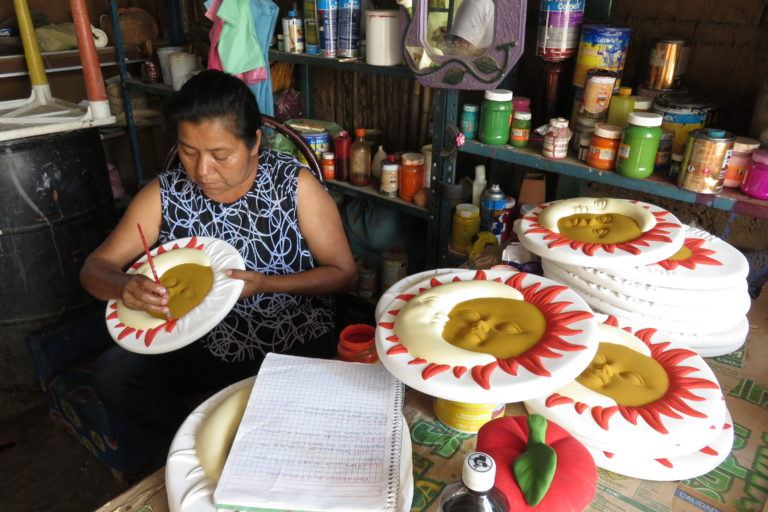 Photograph of a Mexican woman painting clay molds of the sun and moon.