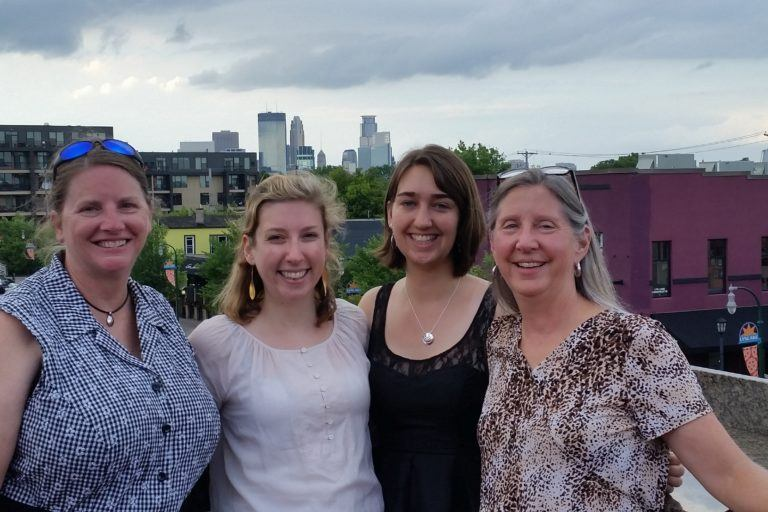 Photograph of four women on a rooftop with the Minneapolis skyline in the background.