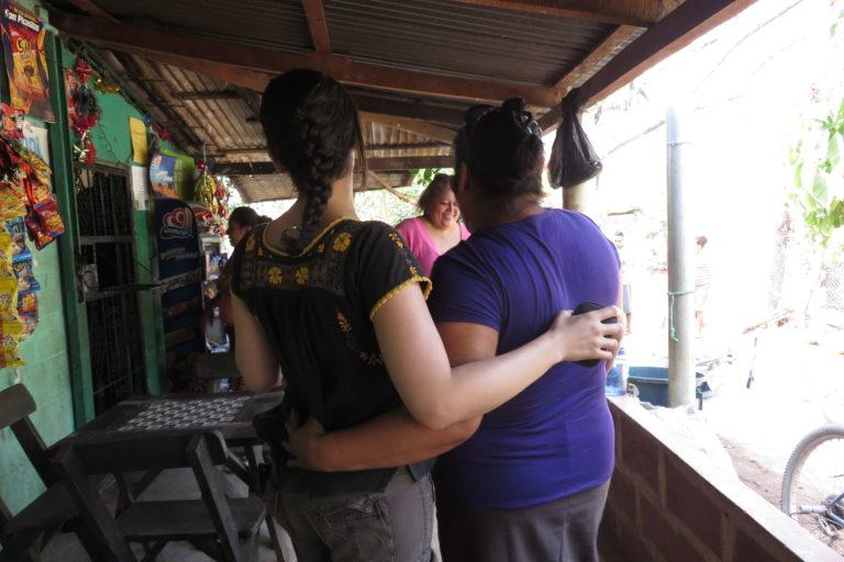 Photograph of two women with their arms around each other.