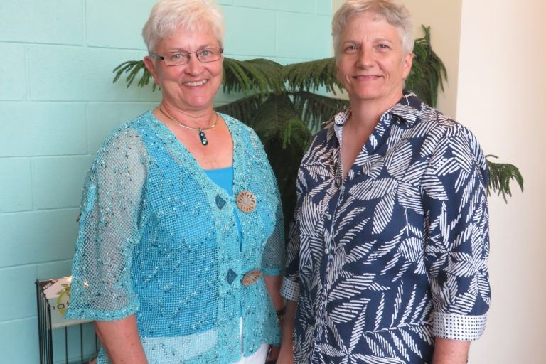 Photograph of two women in their sixties in bright tops and white pants.
