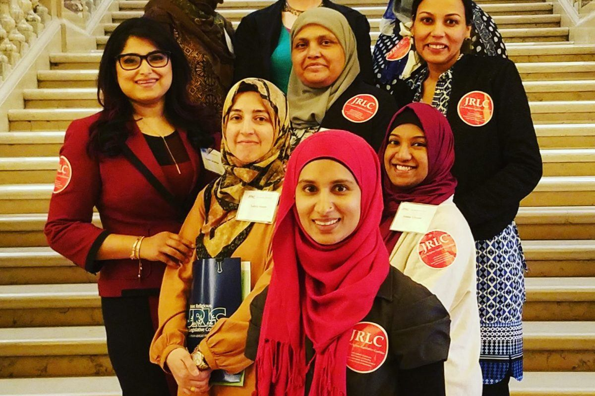 Photograph of nine young muslim women leaders from RISE, standing on steps.