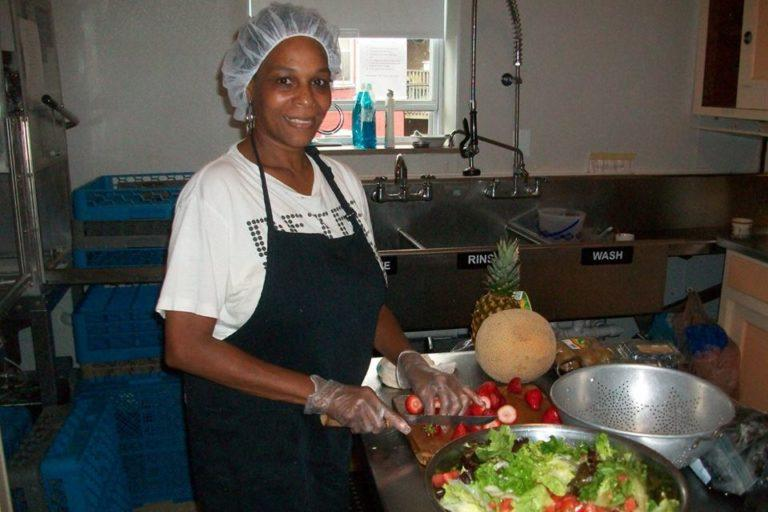A woman with hairnet, aprons, and gloves chopping vegetables for a salad in a kitchen.
