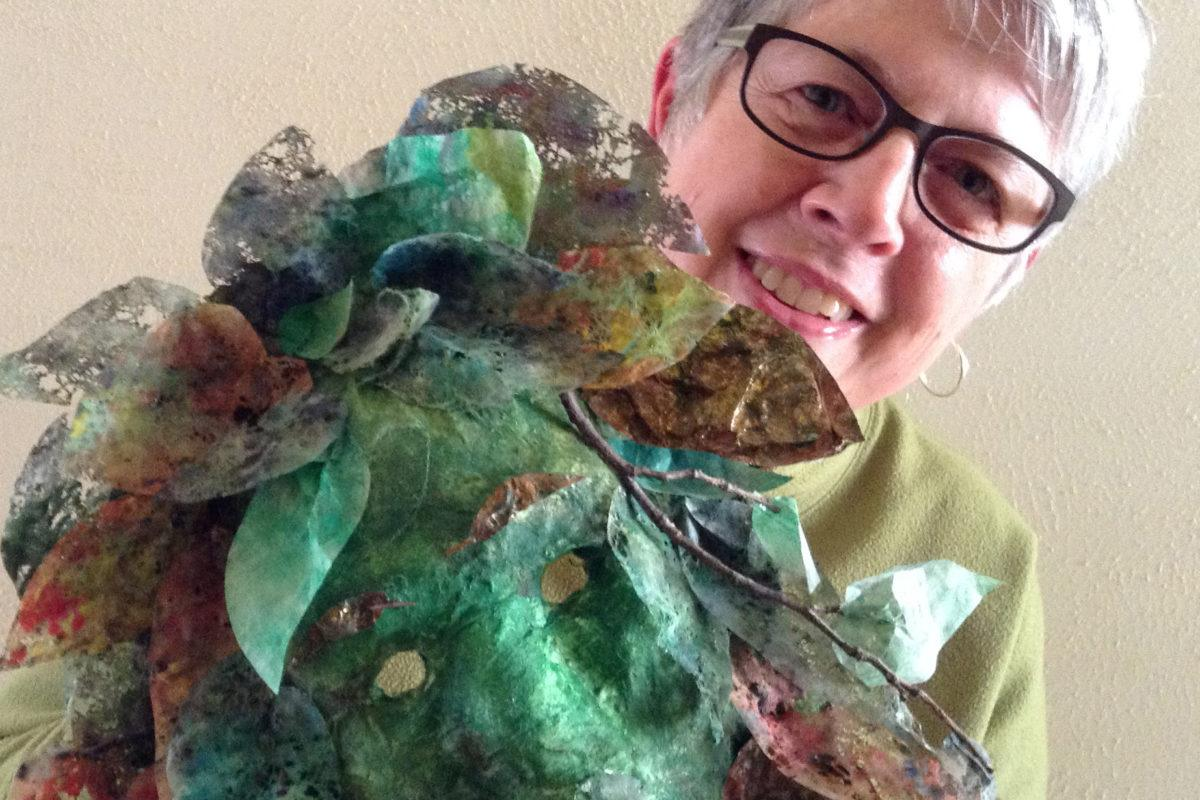 Photograph of Chris Thomas holding a green fiber art mask called Forest Woman.