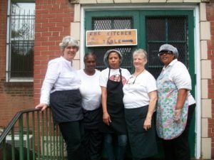"Photograph of five women, two with aprons nad hairnets, on steps in front of a sign that says ""the kitchen table."""