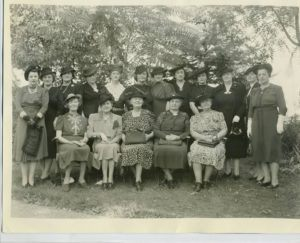 Old photo of a group of women from 1940s at a tea party.
