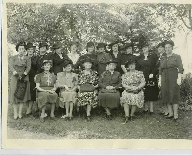 Old photograph of women dressed in victorian clothing, posing in two rows..
