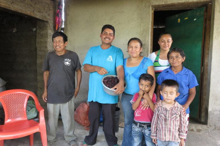 Photograph of a family outside their home near Suchitoto. Grandfather, father, mother, and four children.