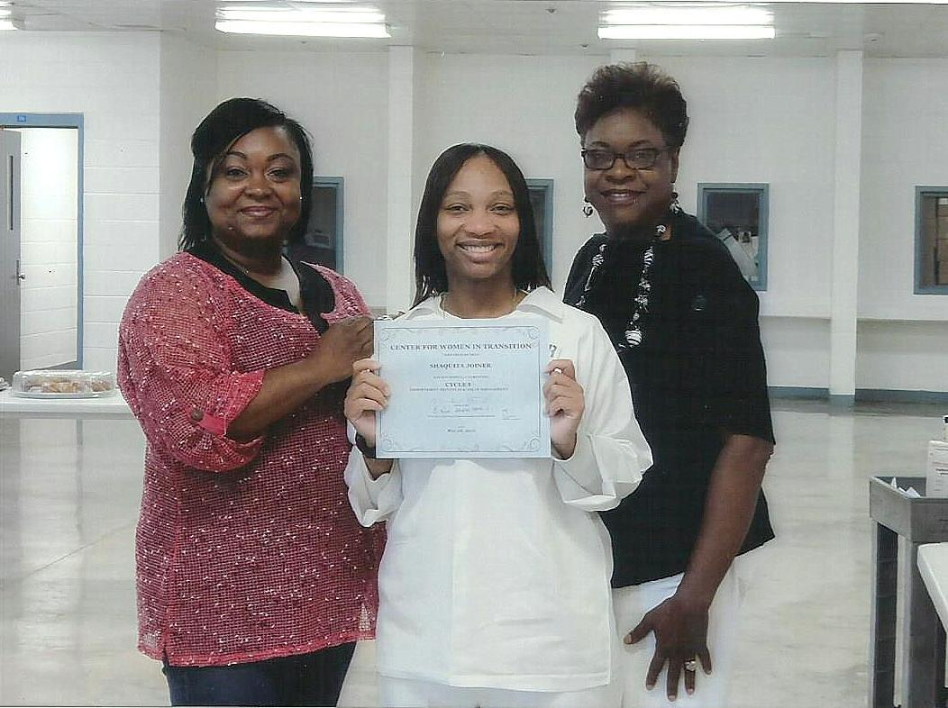 Photograph of three women, the one in the middle is dressed in a prison uniform and holding up a diploma.