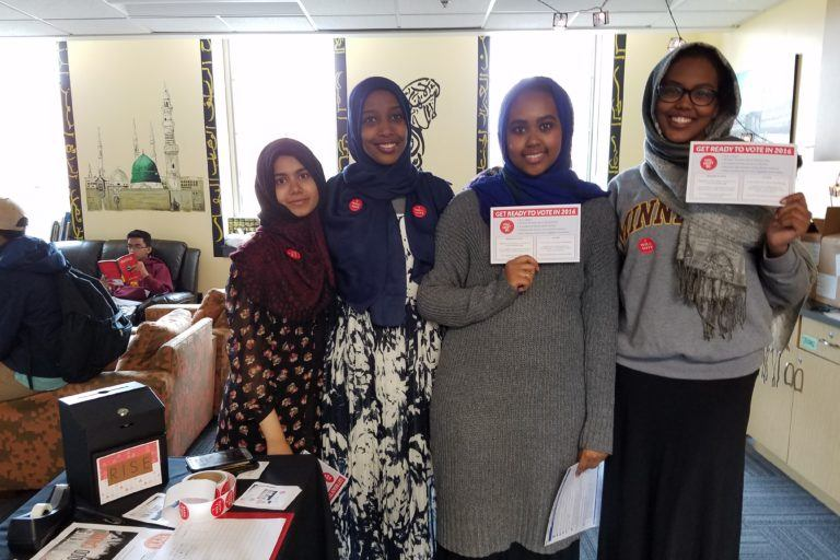 "Photograph of four young women wearing headscarves holding up signs that say ""I voted"""