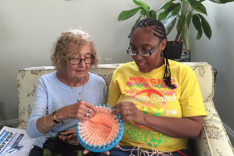 Photograph of two women in glasses sitting on a couch and making a basket together.