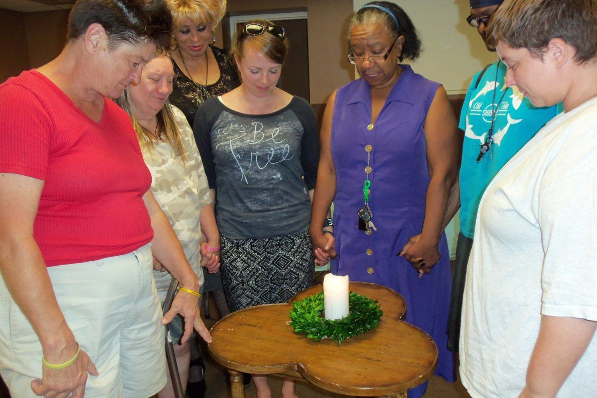 Photograph of seven women standing with their eyes closed and heads bowed around a small table with a candle on it.