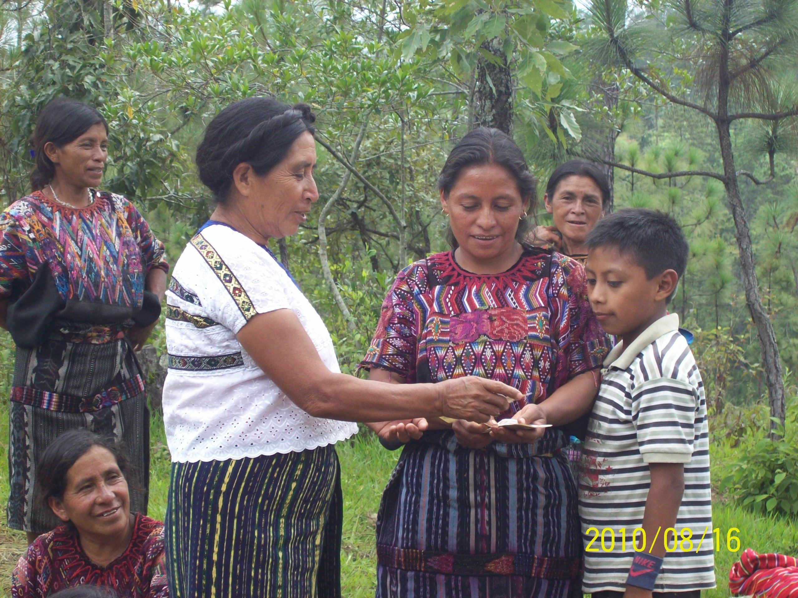 Photograph of a woman handing another woman a loan while her son looks on.