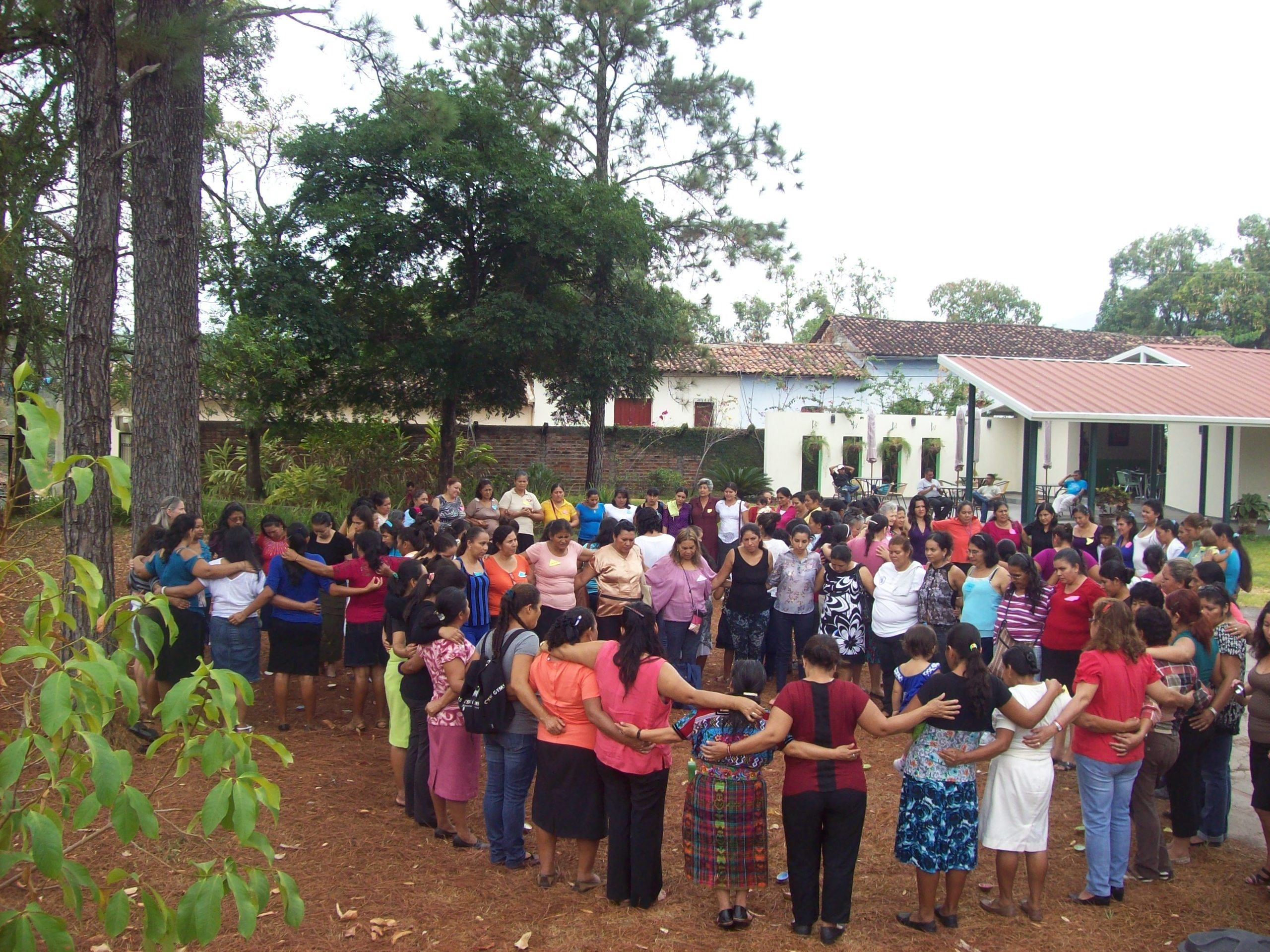 A large group of women standing outside in a circle wiht their arms around each other.