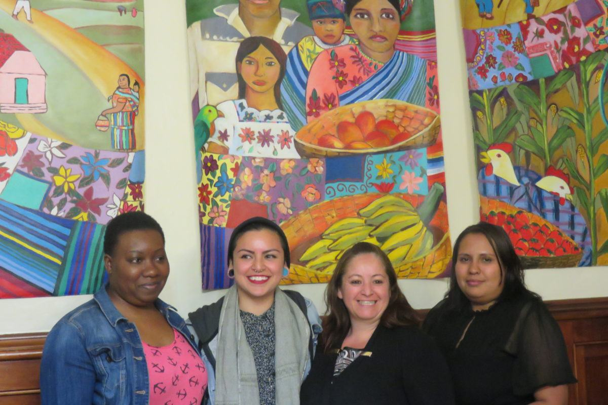 Photograph of four women with a bright wall mural of a mother and daughter holding a tray of food behind them.
