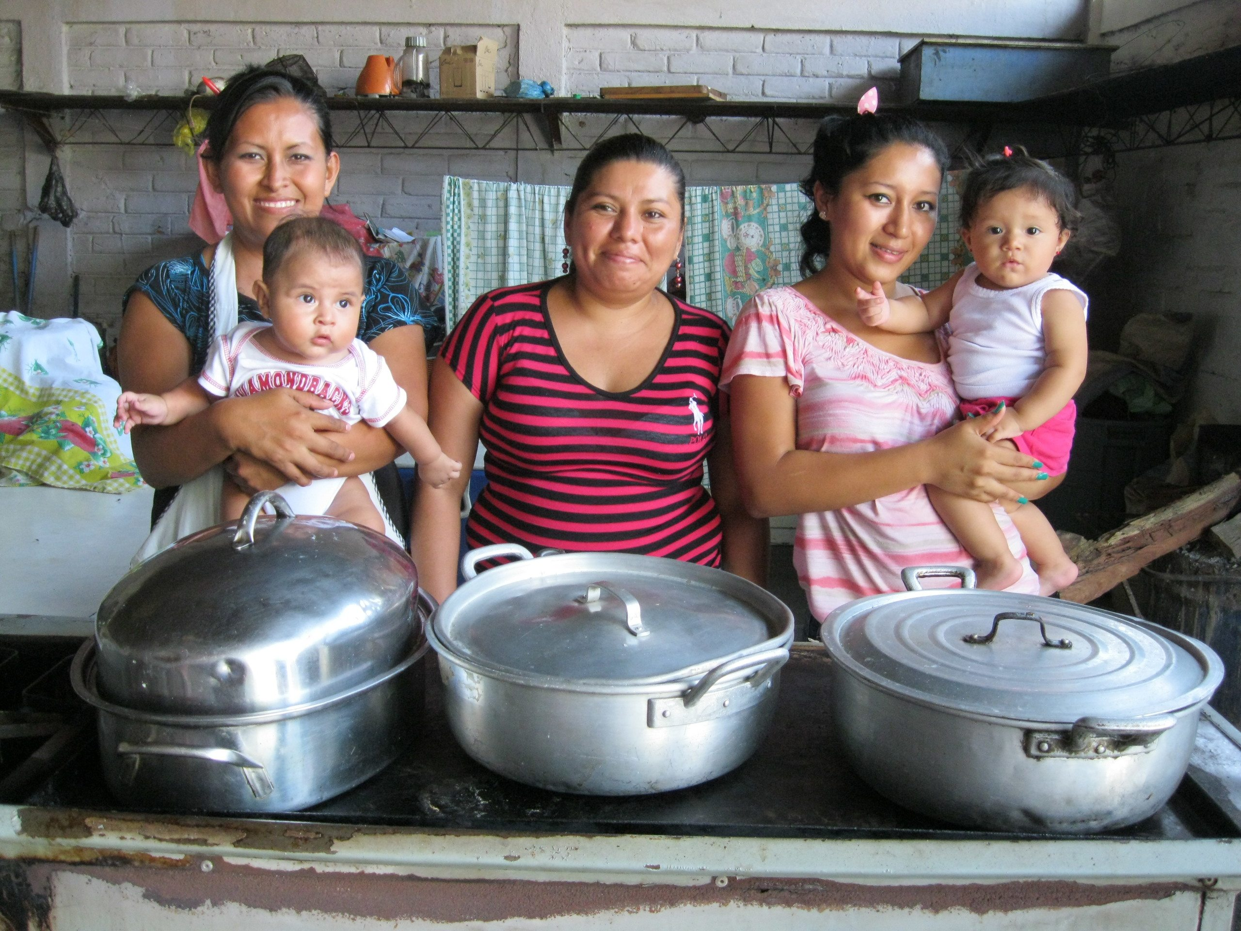 Photograph of three women, two of whom are holding babies, with three large cooking pots in front of them.