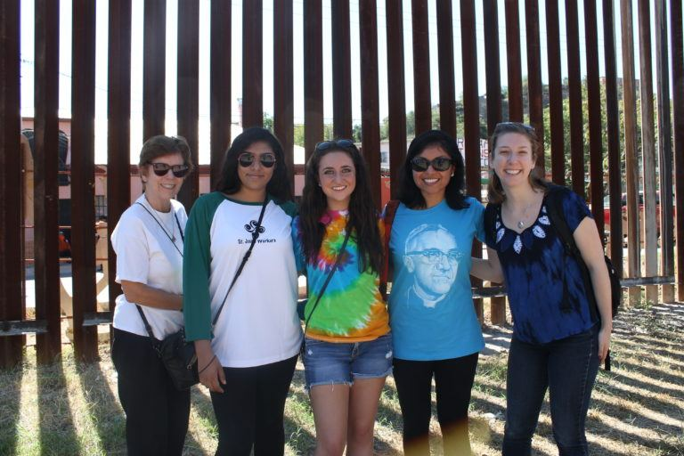 five young women in front of the US/Mexico border fence at the 2016 SOA Convergence at the Border