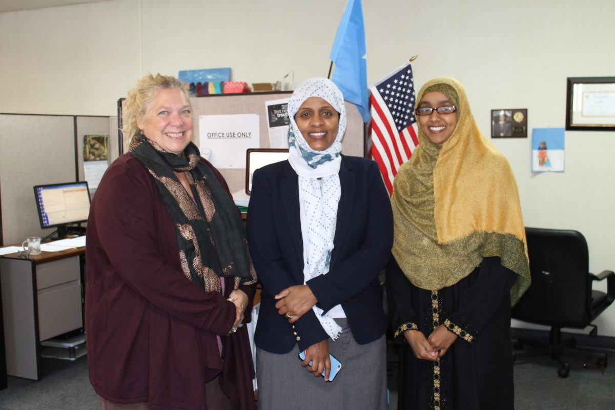 A white woman and two Somali women at the Isuroon office.