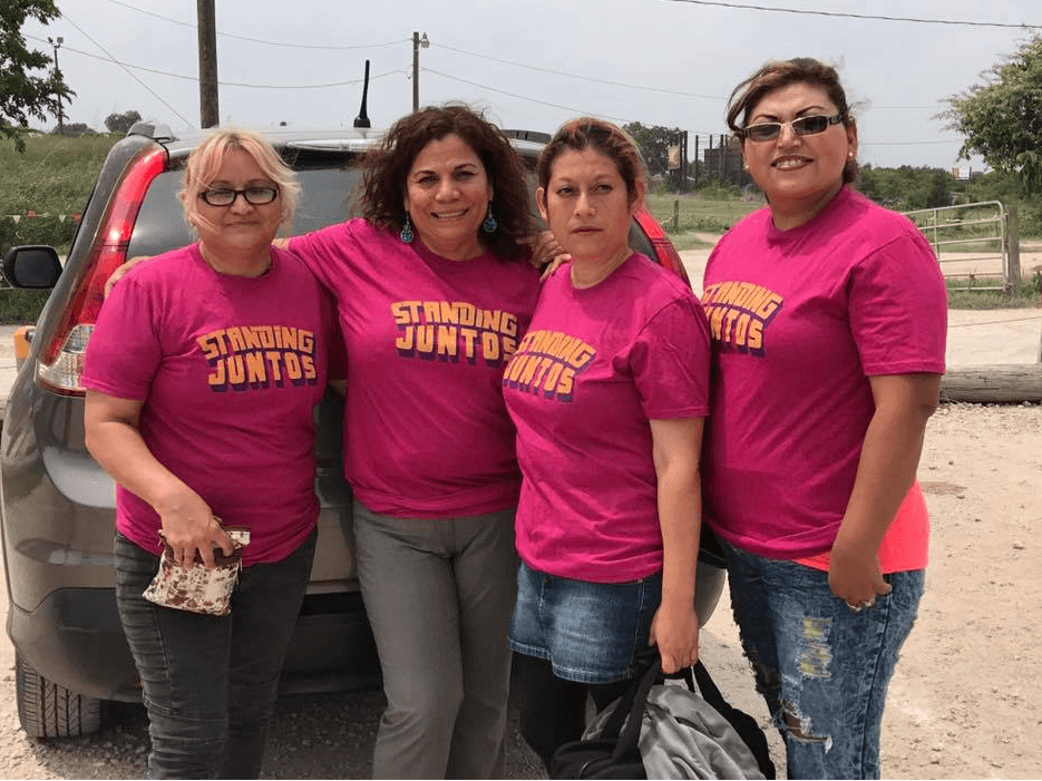 "Group of four women wearing pink tshirts that say ""standing juntas"""