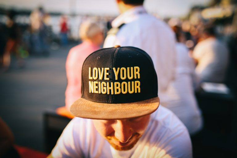 "Photograph of a man wearing a hat that says ""love your neighbor"""