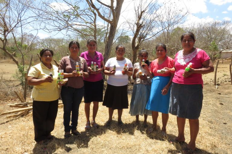 Group of women standing outside in a barren landscape in a semicircle holding up shampoos and soaps.