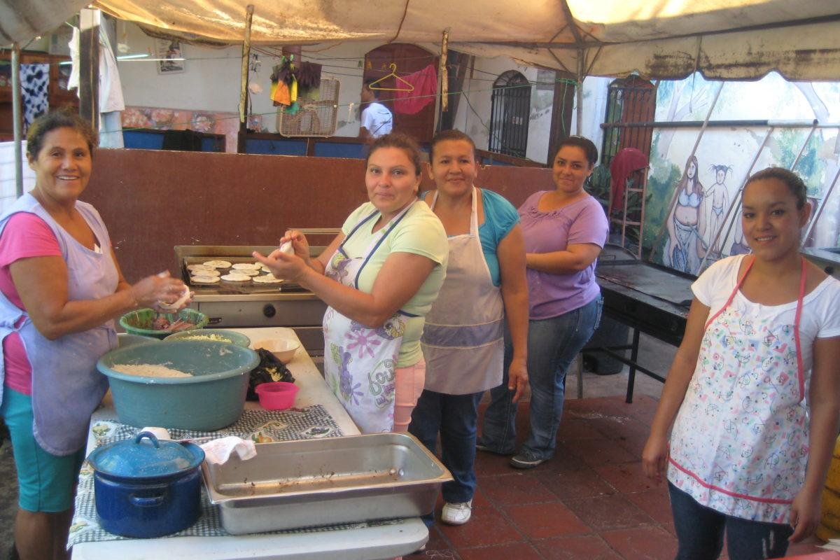 Women with aprons on all in different stages of making tortillas. Some are mixing dough, some are putting them on a grill.