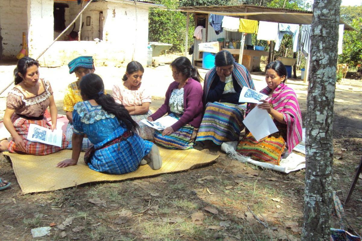 Photograph of a women in traditional guatemalan dress sitting on the ground on mats writing on papers.