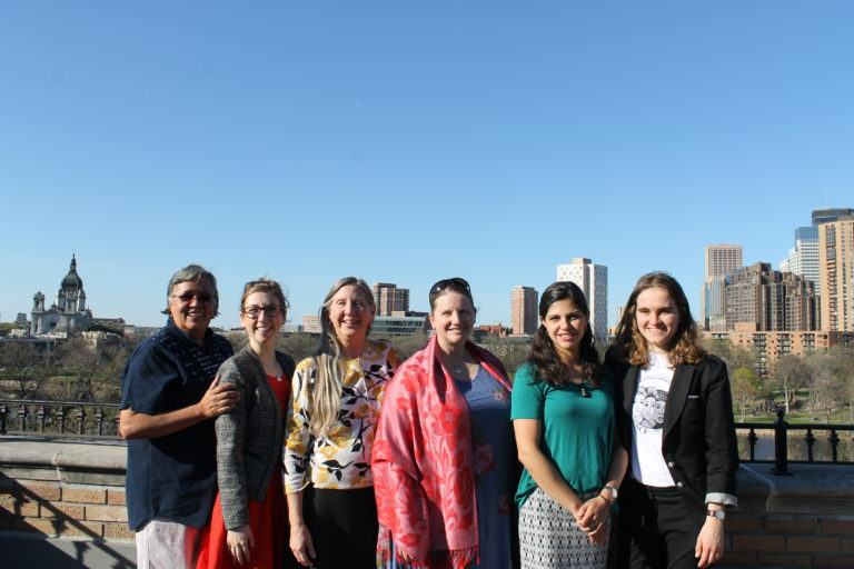 Photograph of Mary's Pence staff with the Minneapolis skyline in the background.