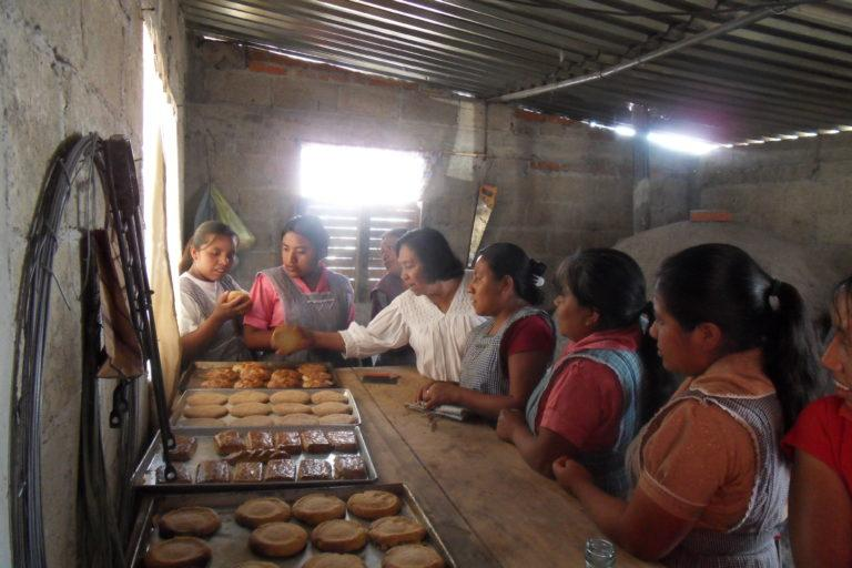 Photograph of several women in aprons around a high counter with baked bread on it.