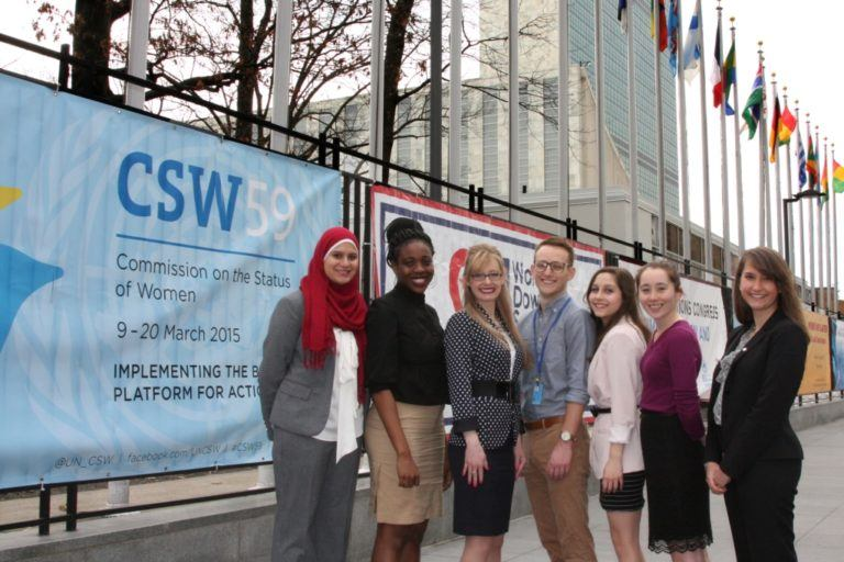 A group of six young women and one man stand in front of the United Nations with flags from various nationalities in the background and a poster that says CSW 59 Commission on the Status of Women