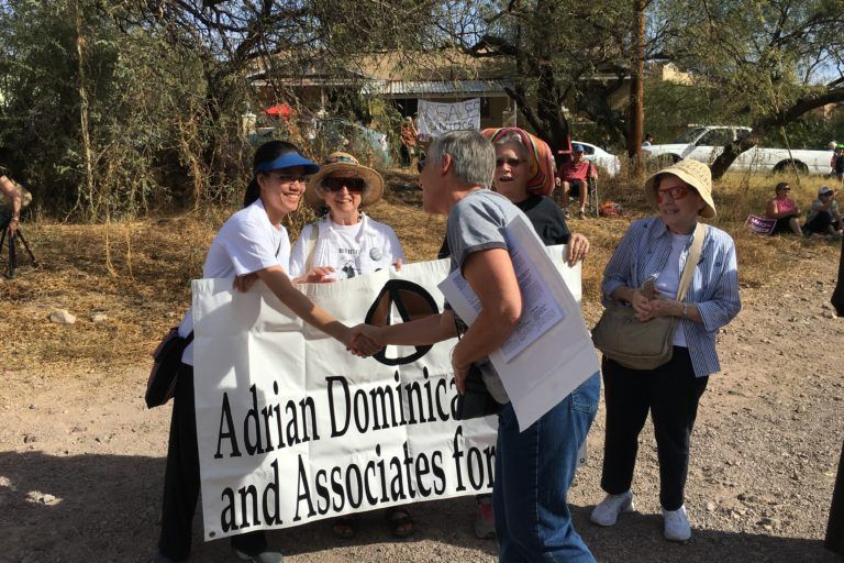 A woman shakes hands with another woman holding up a sign that says Adrian Dominicans and Associates for Peace