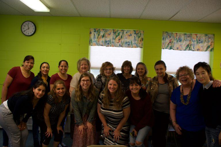 A diverse group of 15 women poses in two rows for the camera in a classroom.