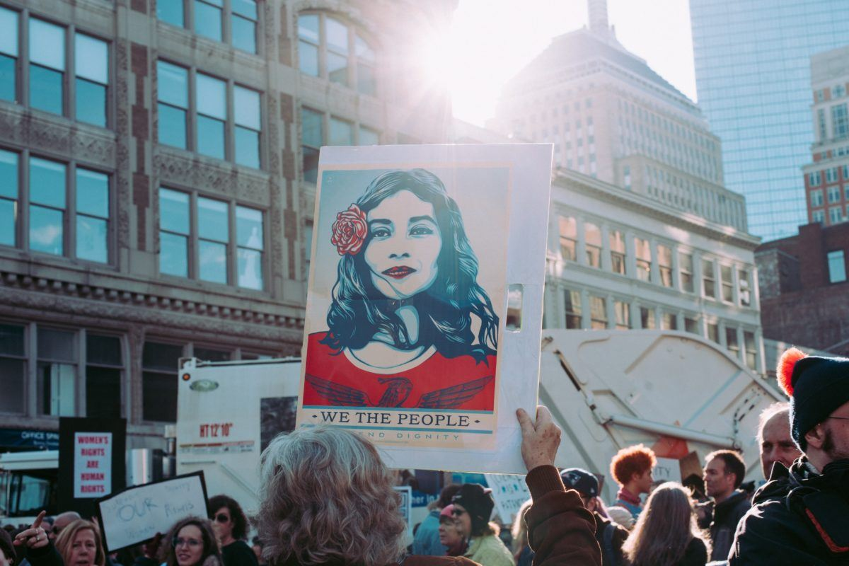 "Photograph of a sign at a protest that features a latina woman with the phrase ""we the people"""