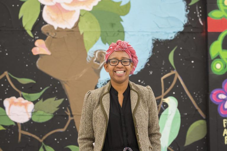 Photo of Nekessa Julia Opoti standing in front of a mural of the profile of a woman. Nekessa wears a red scarf on her head and glasses, and has a big smile.