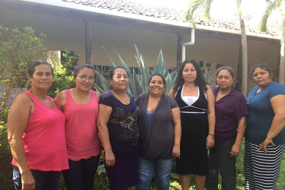 Photograph of the seven women leaders of Concera standing outside their building.