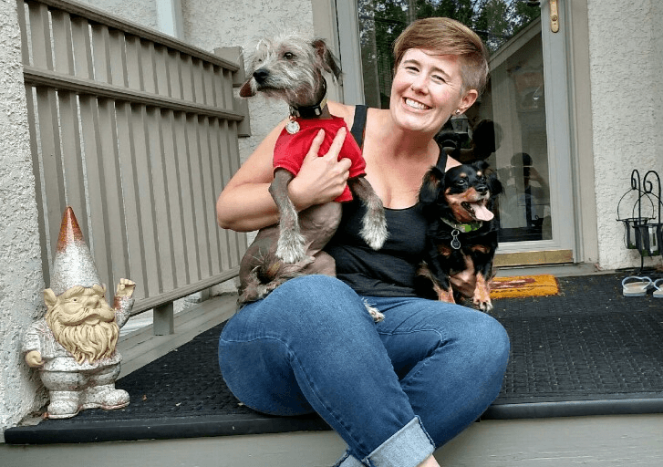Robyn sitting on her front porch casually, smiling and holding her two small dogs.