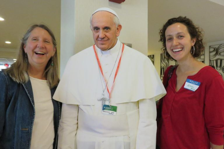Photograph of Mary's Pence executive director Katherine Wojtan and another staff member laughing as they pose with a life-size cut out of Pope Francis.