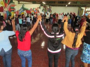 Many women are dancing in a circle, holding hands with their arms raised.