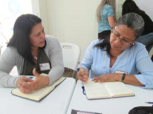 Two women sit together at a table with open notebooks. One woman is speaking while the other is listening and taking notes.