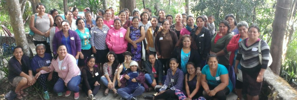 Photograph of the whole group of women participants in the ESPERA emotional health workshop. All are standing or sitting outside and are wearing nametags.