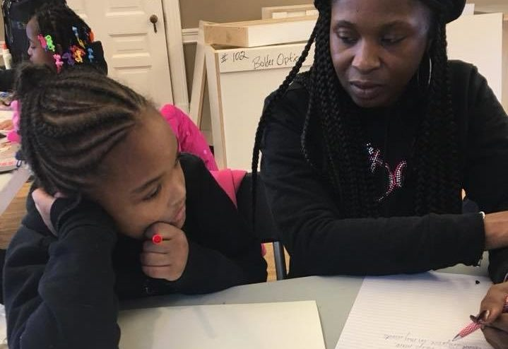 Photo of a black woman helping a young black girl on a writing project.
