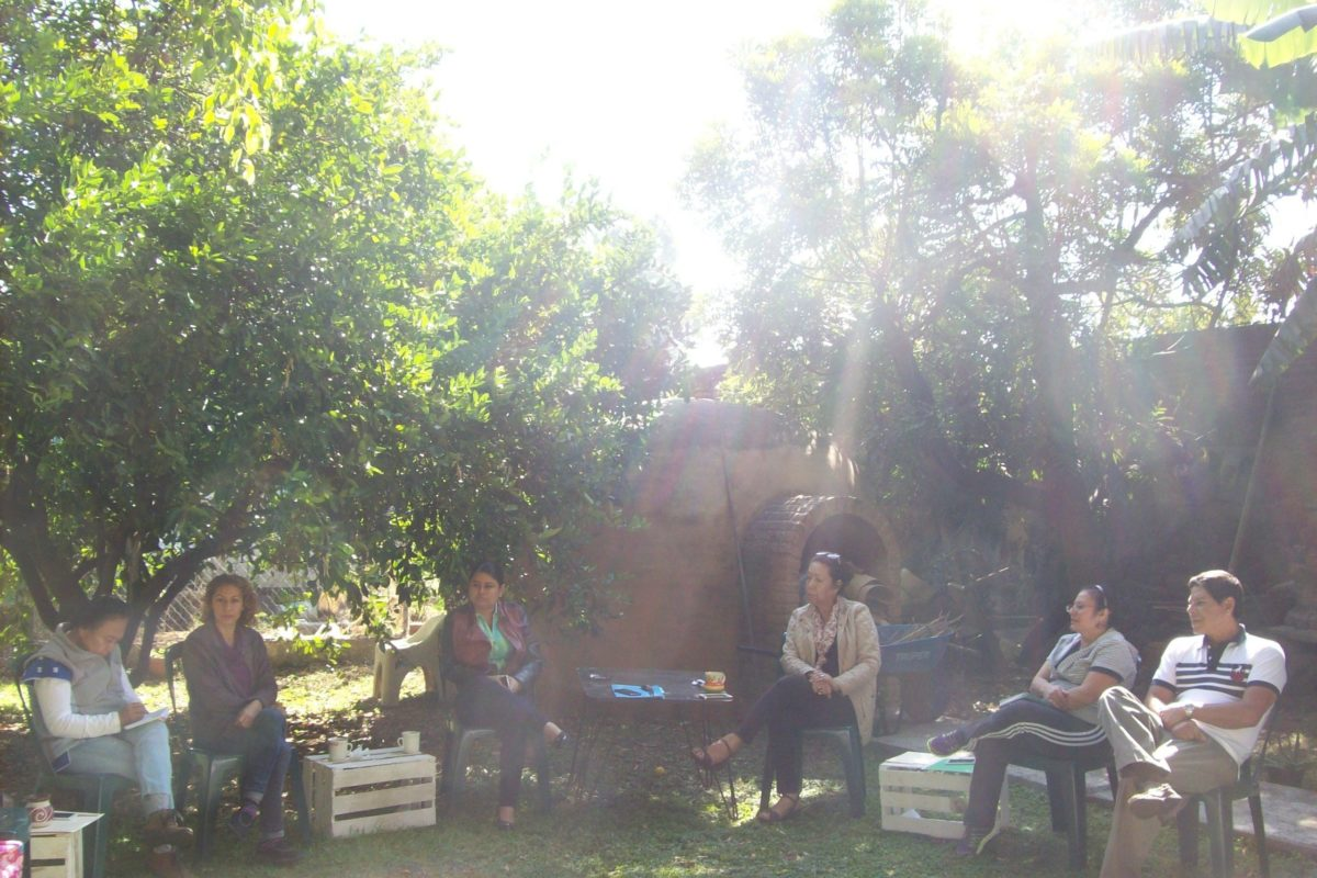 Several people sit outside on chairs with the Temazcal (steam bath) in the background.