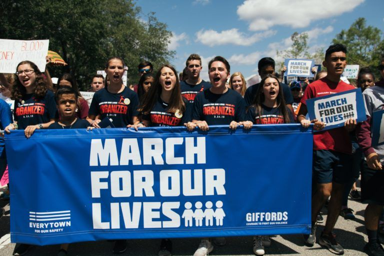 "Photograph of many students marching outside and holding a blue sign reading ""march for our lives"""