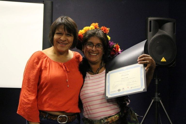 Photo of two women embracing, holding up a certificate of achievment.