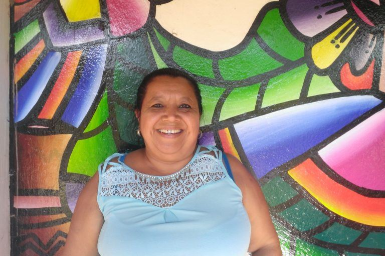 A middle aged woman smiles broadly, she is standing in front of a wall painted in bright colors in the traditional salvadoran style.