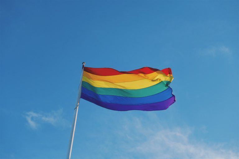 Photograph of LGBTQ+ Pride Flag waving against a clear blue sky.