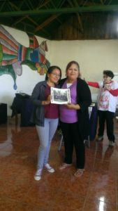 An ESPERA staff member hands a participant in the workshop a certificate of completion, which she holds while smiling proudly.