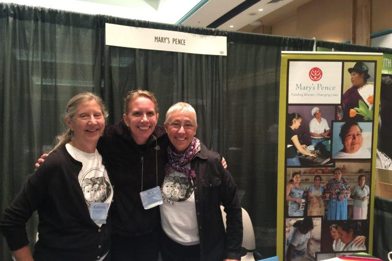 Photograph of three woman standing at a Mary's Pence exhibit booth. Two women are wearing Mary's Pence t-shirts.