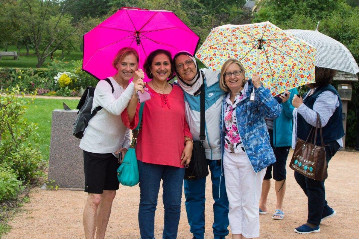 Four women - 2 iraqi, 2 white americans - smile with their arms around one another. The women on the ends hold umbrella's over the group.